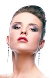 Glamorous model. Gorgeous woman with long earrings looking at camera Royalty Free Stock Photography