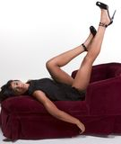 Glamorous model Afro American woman on red couch. Portrait of a beautiful black glamour African American female in black dress lying down on red sofa with legs Royalty Free Stock Images