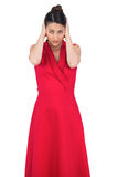 Glamorous model in red dress covering her ears Stock Photo