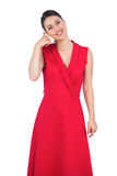 Glamorous model in red dress making phone call gesture Stock Images