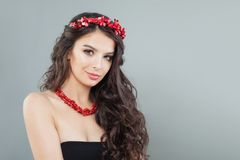 Glamorous model woman with curly hair and coral jewelry.  royalty free stock photo