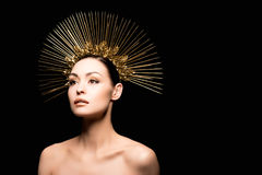 Glamorous naked model posing in golden headpiece. Isolated on black Stock Photos