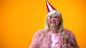 Glamorous old lady in pink coat and party hat celebrating good news, positivity royalty free stock images