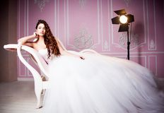 Glamorous photo of a beautiful brunette bride in a luxurious wedding dress lying on pink sofa Stock Photo