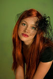 Glamorous redhead. Glamorous studio portrait of a green-eyed redhead young woman, dressed in black and wearing a black netted headpiece over the upper part of Royalty Free Stock Photo