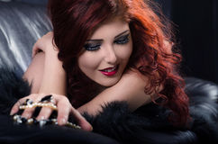 Glamorous redhead woman playing with pearls on leather couch Royalty Free Stock Photography