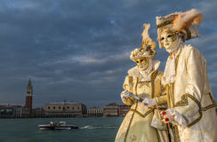 Glamorous and romantic aristocrat couple during venice carnival. Glamorous, elegant and romantic aristocrat couple with golden costume and beautiful venetian Stock Image