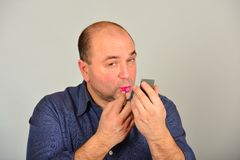 Glamorous and adult man in a shirt, straightens makeup on his face, the concept of gender equality.  stock photo