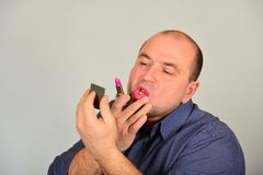 Glamorous and adult man in a shirt, straightens makeup on his face, the concept of gender equality.  stock photography