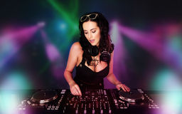 Glamorous sexy busty DJ. At work mixing sound on her decks at a party or night club with colourful strobe light background Royalty Free Stock Photo