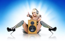 Glamorous sexy party girl with speaker. Glamorous sexy party girl in headphones with speaker, happy sound concept Royalty Free Stock Photo