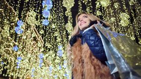 Glamorous smiling woman wearing fur coat with Christmas shopping bag at yellow lights background