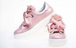 Glamorous sneakers concept. Cute shoes on white background. Pair of pale pink female sneakers with velvet. Ribbons. Footwear for girls and women decorated with stock images