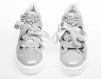 Glamorous sneakers concept. Pair of pale pink female sneakers with velvet ribbons. Footwear for girls and women. Decorated with pearl beads. Cute shoes isolated royalty free stock photos