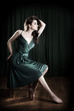 Glamorous Woman. A glamorous young woman sitting on a stool and looking to the light Royalty Free Stock Images