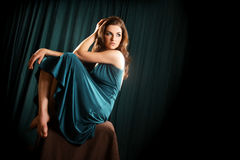 Glamorous Woman. A glamorous young woman sitting on a stool and looking to the side Royalty Free Stock Photos