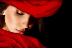 Glamorous woman. Image of glamorous woman wearing stylish floral hat, closeup portrait of beautiful arabic female with red rose on head isolated on black Stock Image