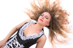 Glamorous Woman. A glamorous woman with hair spread lying on a white floor Stock Images