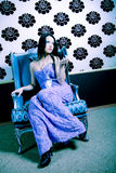Glamorous Woman. A glamorous young woman in a lavender dress sitting on a luxurious chair Royalty Free Stock Photo