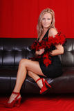 Glamorous woman. Glamorous blond woman wearing a black dress, red shoes and a feather boa, sitting on a leather sofa Stock Photo