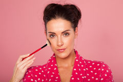Glamorous woman applying blusher stock photo