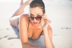 Glamorous woman in bikini lying on the beach Stock Photo