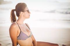 Glamorous woman in bikini sitting on the beach Stock Image