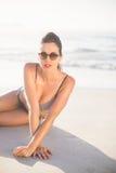 Glamorous woman in bikini sitting on the beach Royalty Free Stock Photography