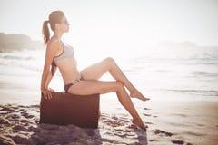 Glamorous woman in bikini sitting on an old suitcase Stock Photo