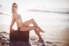 Glamorous woman in bikini sitting on an old suitcase Royalty Free Stock Photo