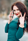 Glamorous woman in a bright emerald dress talking on the phone, smiling, showing thumbs up world to nail red varnish Stock Photography