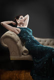 Glamorous woman on chaise lounge. Wearing sparkly dress stock image