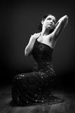 Glamorous woman dancing. Glamorous woman in a blue sparkly dress dancing/posing. Black and white. Dramatic lighting royalty free stock photos