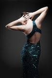 Glamorous woman dancing. Glamorous woman in a blue sparkly dress dancing/posing. Dramatic lighting royalty free stock photography
