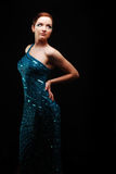 Glamorous woman dancing. Glamorous woman in a blue sparkly dress dancing/posing. Dramatic lighting royalty free stock images