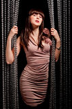 Glamorous woman in dress posing near curtains Royalty Free Stock Images