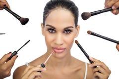 Glamorous woman encircled by make up brushes. On white background Royalty Free Stock Image