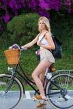 Glamorous woman enjoying recreation time while strolling on bicycle Royalty Free Stock Images