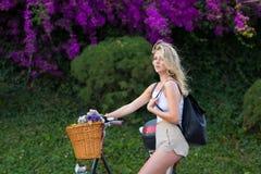 Glamorous woman enjoying recreation time while strolling on bicycle Royalty Free Stock Image