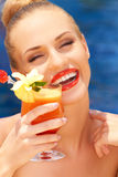 Glamorous woman enjoying a tropical cocktail Stock Photography