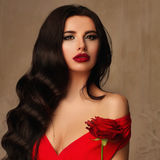 Glamorous Woman Fashion Model with Long Permed Hairstyle. Red Lips Makeup and Red Rose Flower Royalty Free Stock Photos