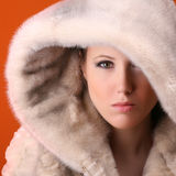 Glamorous woman with fur. Portrait of glamorous woman with fur isolated on orange background Stock Image