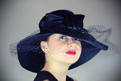 Glamorous woman in the hat. Woman in a glamorous vintage hat posing Royalty Free Stock Photography