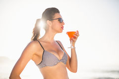 Glamorous woman having a cocktail drink on the beach Royalty Free Stock Photography
