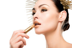 Glamorous woman in headpiece applying golden lipstick. Isolated on white Royalty Free Stock Photos