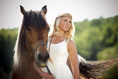 Glamorous woman with horse. A glamorous woman in long white dress with her horse Royalty Free Stock Photos