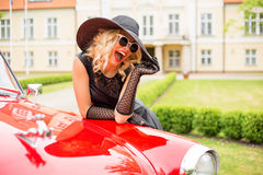 Glamorous woman leaning on red vintage car Royalty Free Stock Photo