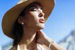 Glamorous woman looking towards the sun. While wearing a hat Stock Image