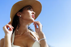 Glamorous woman looking towards the sun. While wearing a hat Stock Photos