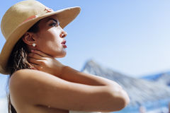 Glamorous woman looking towards the sun. While wearing a hat Stock Photography